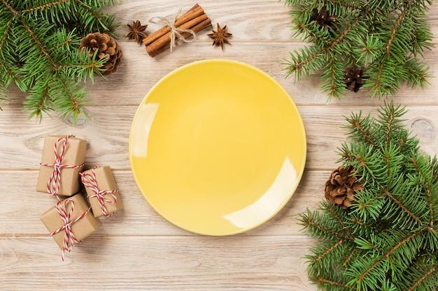 Pusty żółty matte talerz na drewnianym. z świąteczną dekoracją, okrągłe naczynie. nowy rok
