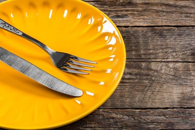 Pusty żółty porcelanowy talerz, nóż i widelec na drewnianym tle