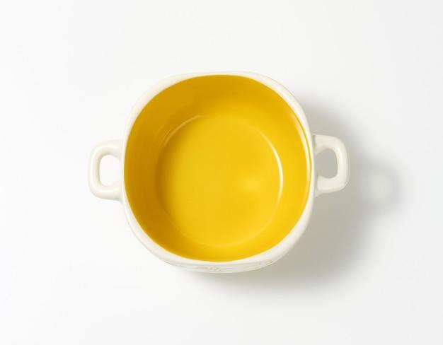 Pusty żółty talerz zupy na białym stole, widok z góry