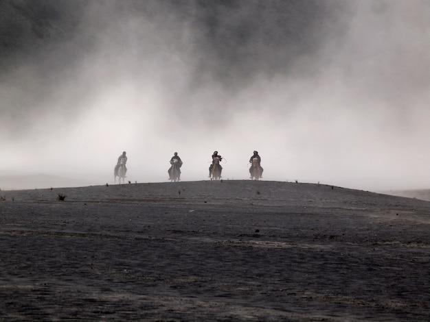 Pustynia bromo i jeźdźcy koni podczas burzy piaskowej w bromo