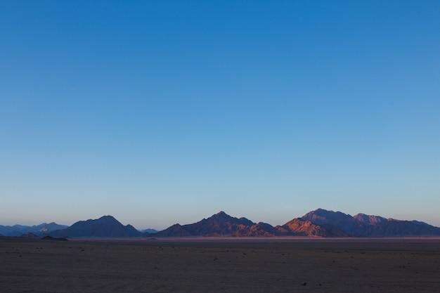Pustynia egiptu w zachodzących słońcem górach i piasku