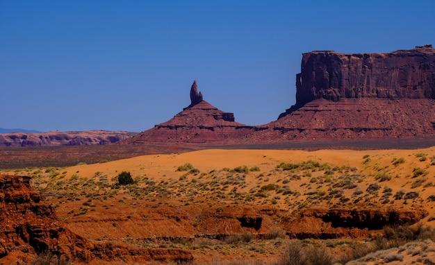 Pustynne wzgórze z suszonymi krzakami i klifami w oddali w słoneczny dzień