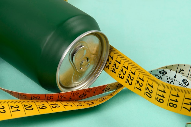 Puszka aluminiowa w kolorze zielonym z kolorową miarką symbolizującą osobę chcącą schudnąć g.
