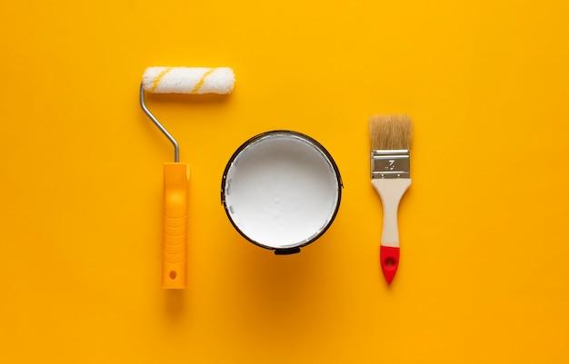 Puszka białej farby z pędzlem i wałkiem na żółtym tle. narzędzia do malowania i renowacji.