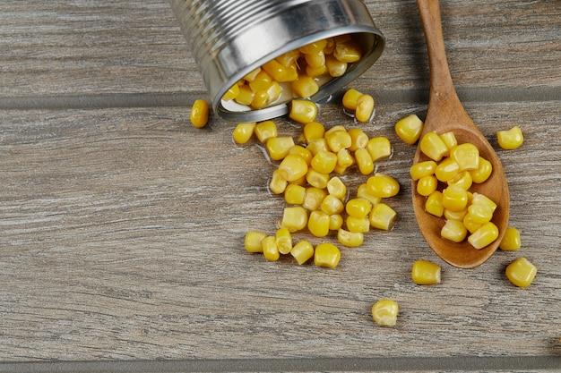 Puszka gotowanej kukurydzy na drewnianym stole z łyżką.