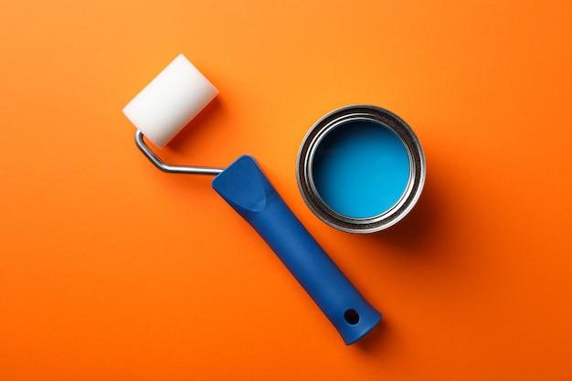 Puszka niebieskiej farby i wałek na pomarańczowej powierzchni