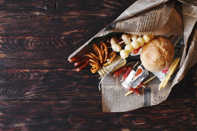 Puszka piwa z przekąską na drewnianym ciemnym tle. bukiet prezentów dla mężczyzny. prezent świąteczny dla mężczyzn