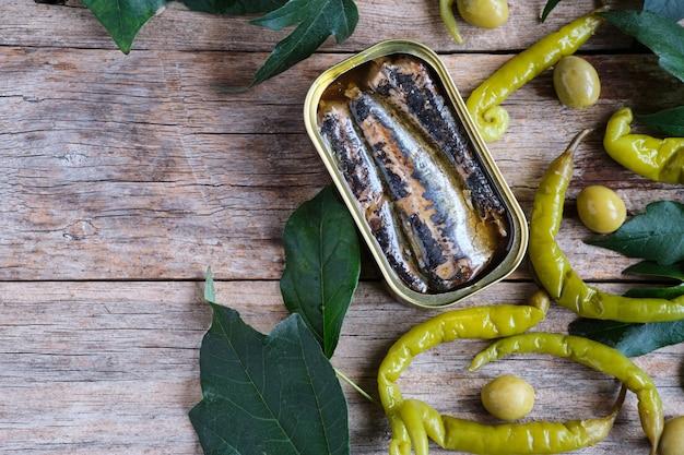 Puszka sardynek w oleju z chilli i oliwkami na rustykalnym drewnianym stole i przestrzeni kopii