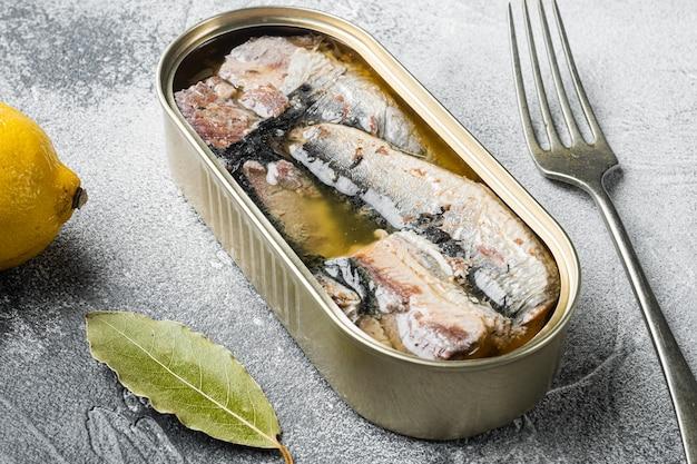 Puszka sardynek w zestawie oliwy z oliwek, na szarym tle kamiennego stołu