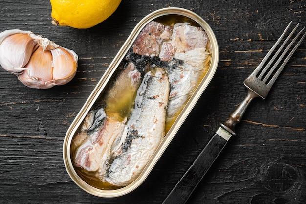 Puszka sardynek w zestawie oliwy z oliwek, na tle czarnego drewnianego stołu, widok z góry płaski lay