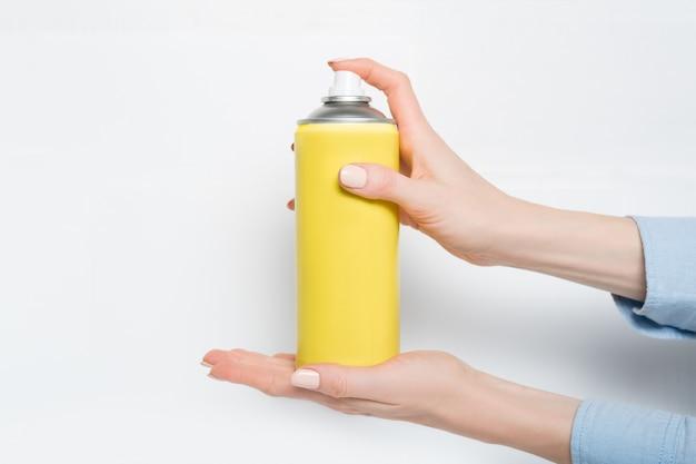 Puszka z żółtym sprayem do rozpylania w rękach kobiet.