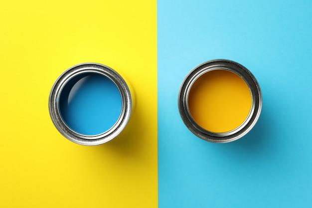 Puszki błękitna i żółta farba na dwa brzmień tle, odgórny widok