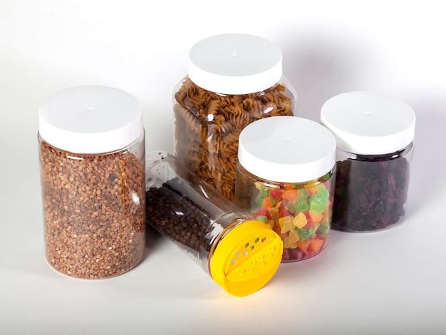 Puszki do przechowywania produktów luzem z żywnością na na białym tle. przezroczysty plastikowy pojemnik z pokrywką do przechowywania żywności i produktów sypkich. zboża i produkty luzem w słoikach do celów spożywczych. skopiuj miejsce
