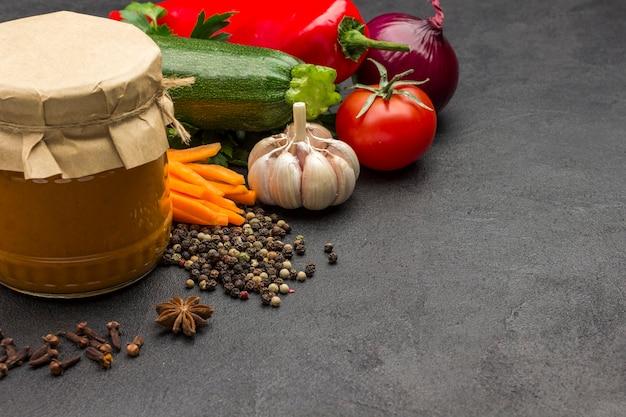 Puszki do smarowania dyni w szklanym słoiku surowe warzywa i przyprawy marchew czosnek cebula pomidory anyż gwiaździsty chili pieprz pieprz pietruszka