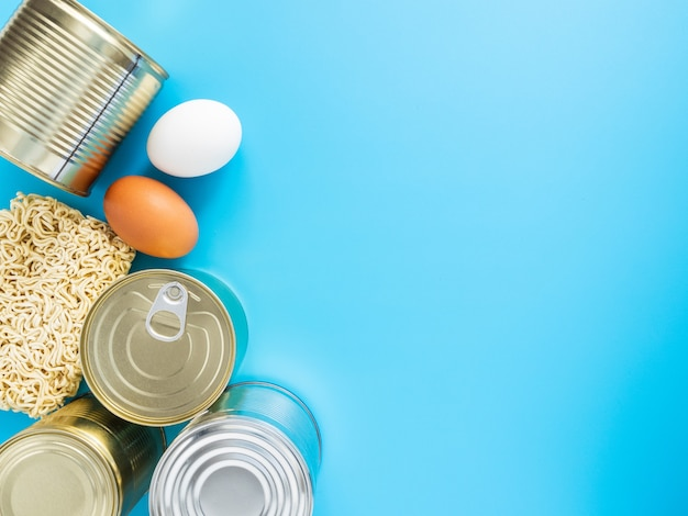 Puszki, makaron, jajka na niebieskim tle, copispace, makieta. zapasy fast foodów i długoterminowe przechowywanie podczas pandemii koronawirusa. koncepcja: zapasy żywności w kwarantannie.