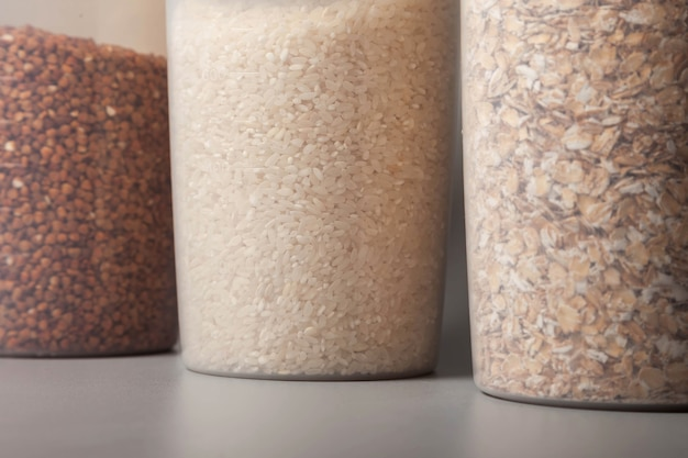 Puszki miarowe o wymiarach 1000 i 400 sześciennych do przechowywania produktów sypkich z żywnością na szarym tle. przezroczysty plastikowy pojemnik do przechowywania żywności i produktów sypkich. zboża i produkty luzem w słoikach