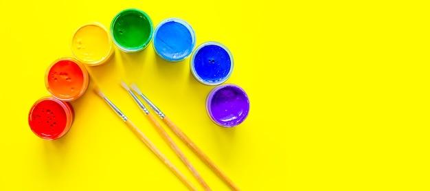 Puszki po farbie ułożone są w półokręgu w formie tęczy z trzema pędzlami na j...