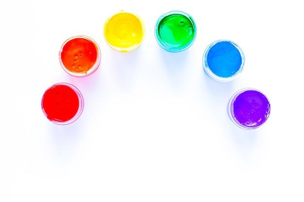 Puszki po farbie wyeksponowane są w półokręgu w formie tęczy na białym tle widok z góry...