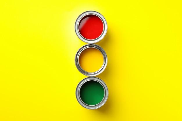 Puszki różnych farb na żółtej powierzchni