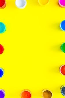 Puszki z farbą są ułożone w prostokąty wzdłuż krawędzi zdjęcia w różnych kolorach na żółto...