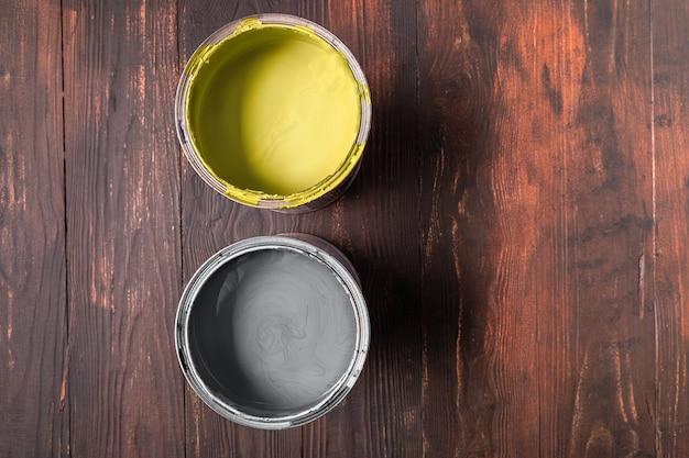 Puszki z farbą w ostatecznym szarym kolorze i rozświetlającym kolorem na brązowym drewnianym tle. kolory roku 2021. skopiuj miejsce na twój tekst. leżał na płasko.