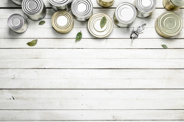 Puszki z jedzeniem i otwieraczem. na białym drewnianym stole.