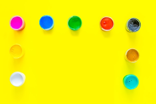 Puszki z wielokolorową farbą znajdują się z boku i na górze zdjęcia na żółtym tle, aby...