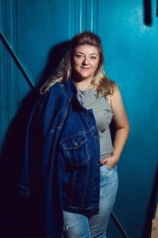 Puszysta kobieta w dżinsowej kurtce i niebieskich spodniach stoi na ulicy przy płocie