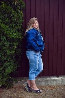 Puszysta Kobieta W Dżinsowej Kurtce I Niebieskich Spodniach Stoi Na Ulicy Przy Płocie Premium Zdjęcia