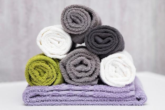 Puszyste bawełniane ręczniki w rolce w różnych kolorach w łazience na białej powierzchni