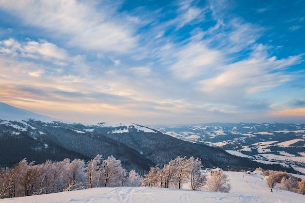 Puszyste chmury schronią się pod białym śniegiem osłonięte lasami i pięknymi górami