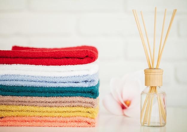 Puszyste ręczniki kąpielowe na jasnym drewnianym stole z patyczkami zapachowymi