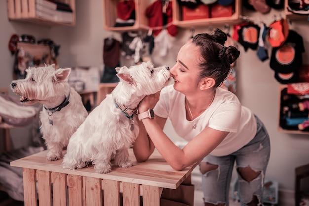 Puszysty biały pies. śliczna ciemnooka kobieta nosząca inteligentny zegarek bawiąca się puszystym białym psem