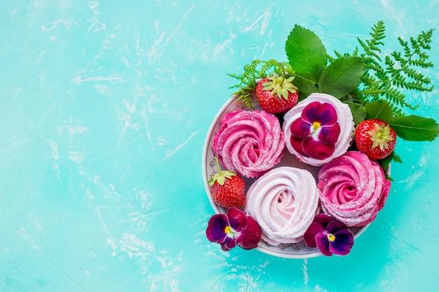 Puszysty deserowy zefir, różowa bezowa zawijas i truskawka. leżał płasko. dzień matki, inne pojęcie uroczystości. piękne słodkie ciasta deserowe. widok z góry.