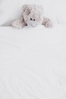 Puszysty pluszowy miś pod dużym kątem w łóżku