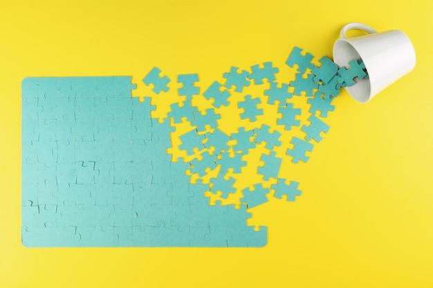 Puzzle i kubek na żółtym tle