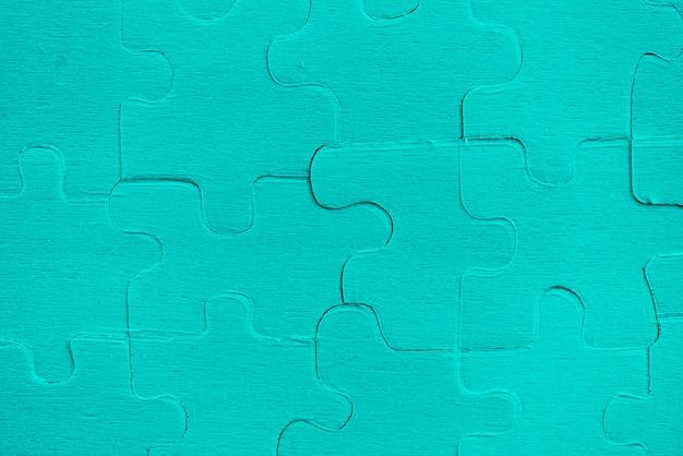 Puzzle jigsaws - niebieskie kawałki układanki na niebieskiej fakturze