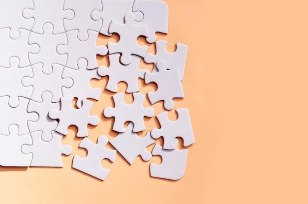 Puzzle nieposortowane elementy na różowym tle, widok z góry