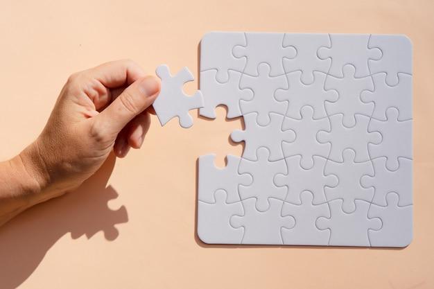 Puzzle nieposortowane elementy na różowym tle z czyjąś ręką trzymającą jeden pokój