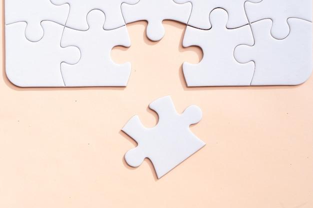 Puzzle z 1 niedopasowanym elementem na różowym tle