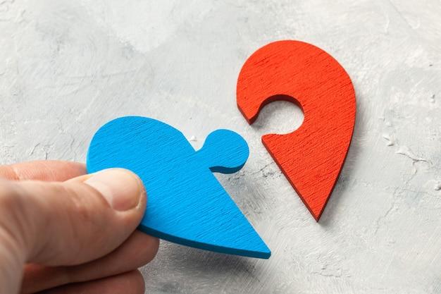 Puzzle z sercem dwie połówki serca mężczyzny i kobiety połączyły się. dwie części miłości. para kochanków. męskiej ręki trzymającej kawałek układanki.