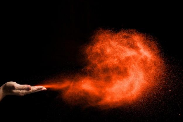 Pył wieje z rąk na czarnym tle. kolor.