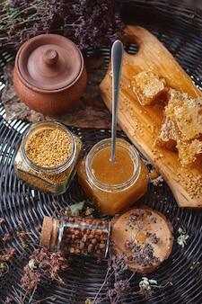 Pyłek i miód w szklanym słoju i plaster miodu na drewnianej desce na wiklinowym stole