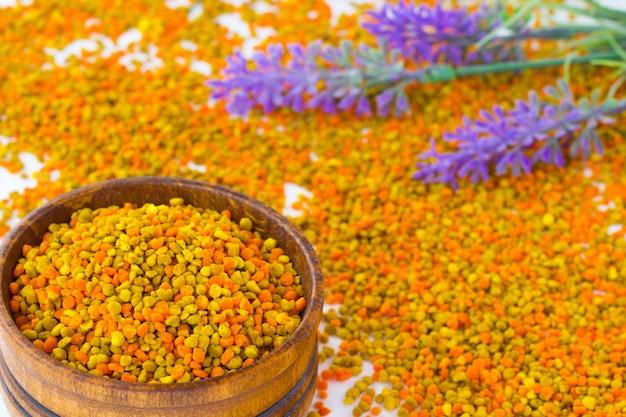 Pyłek kwiatowy w drewnianym pudełku. fioletowe kwiaty leżą na pyłku