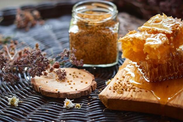 Pyłek w szklanym słoju i plaster miodu na drewnianej desce na wiklinowym stole