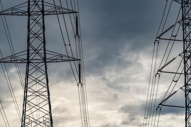 Pylon elektryczny wysokiego napięcia i przewód elektryczny przed burzliwym niebem i chmurami.