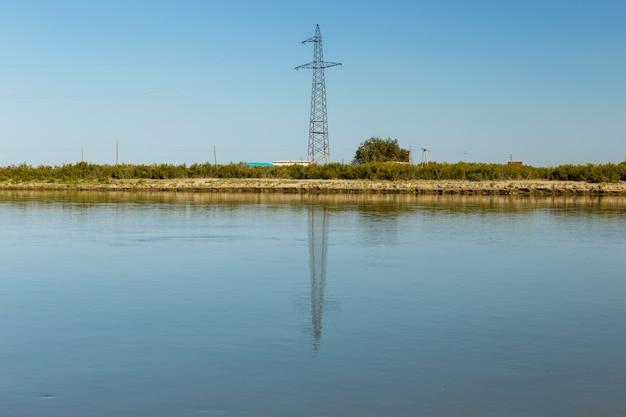 Pylon linii energetycznej stoi nad brzegiem rzeki syr darya, odbite w wodzie, kazachstan. linia energetyczna przecina rzekę