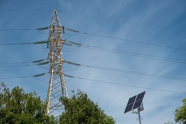 Pylon wysokiego napięcia z panelem słonecznym i zielonymi drzewami.