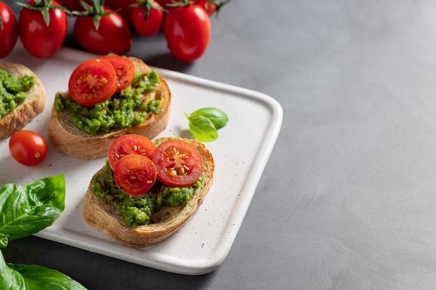 Pyszna Bruschetta Ze świeżym Pesto I Pomidorkami Koktajlowymi Na Ciemnym Tle Włoskie Jedzenie Premium Zdjęcia