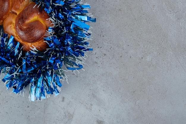 Pyszna bułka zawinięta w niebieski blichtr na marmurowym stole.